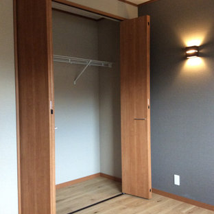 Bild på en mellanstor funkis garderob för könsneutrala, med släta luckor, skåp i mellenmörkt trä, målat trägolv och brunt golv