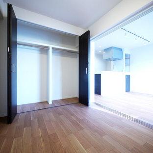 Aménagement d'un placard dressing moderne avec des portes de placard en bois sombre, un sol en contreplaqué, un sol beige et un plafond en papier peint.