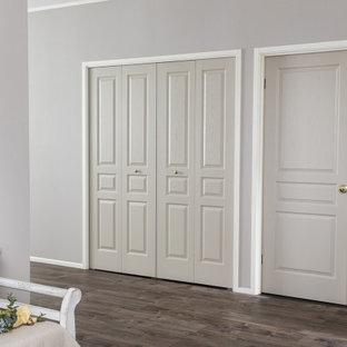 Diseño de armario romántico con armarios con paneles con relieve, puertas de armario beige, suelo laminado y suelo marrón