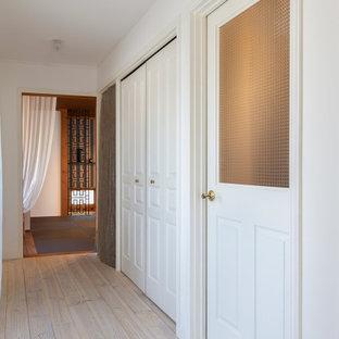 Foto de armario papel pintado, romántico, con armarios con paneles con relieve, puertas de armario blancas, suelo de madera clara, suelo blanco y papel pintado