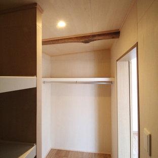 Inredning av ett minimalistiskt litet walk-in-closet för män, med mellanmörkt trägolv och brunt golv