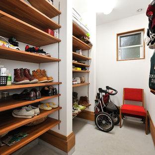 Idee per una cabina armadio country con nessun'anta, ante in legno scuro e pavimento in cemento