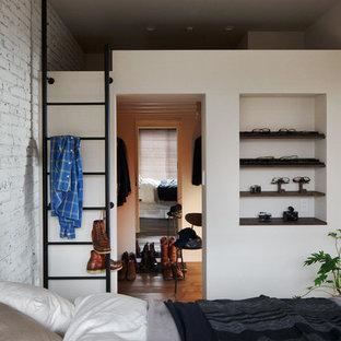 Idee per una cabina armadio per uomo industriale con nessun'anta e pavimento in legno massello medio