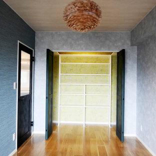 Foto di un piccolo armadio o armadio a muro unisex design con ante bianche, pavimento in compensato, pavimento marrone, ante lisce e soffitto in carta da parati