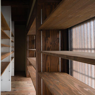 Ispirazione per un armadio o armadio a muro stile shabby di medie dimensioni con ante marroni, parquet chiaro e pavimento marrone