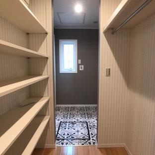 Ejemplo de armario vestidor unisex y papel pintado, nórdico, grande, con armarios abiertos, suelo de madera clara, suelo beige y papel pintado