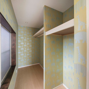 Inredning av ett skandinaviskt litet walk-in-closet för kvinnor, med öppna hyllor, gröna skåp, ljust trägolv och beiget golv