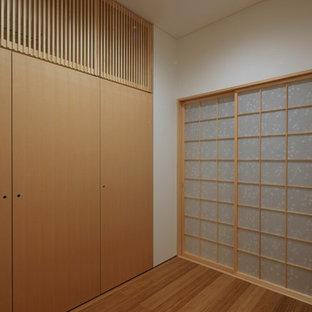 Foto de armario vestidor unisex, asiático, de tamaño medio, con armarios con paneles lisos, puertas de armario beige, suelo de madera en tonos medios y suelo marrón