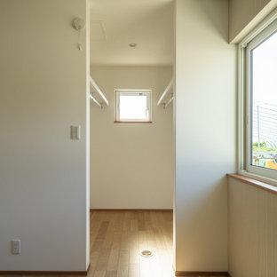 Ispirazione per una cabina armadio etnica di medie dimensioni con ante beige, parquet chiaro e pavimento beige
