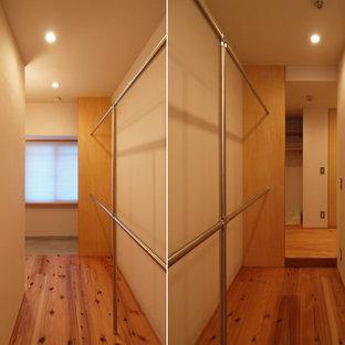 Esempio di una cabina armadio unisex nordica con nessun'anta, ante marroni, pavimento in legno massello medio e pavimento marrone