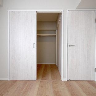 Immagine di una cabina armadio stile shabby con pavimento in compensato e pavimento beige