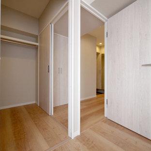 Foto di una cabina armadio shabby-chic style con pavimento in compensato e pavimento beige