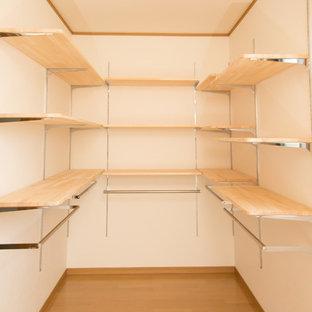 Foto di una cabina armadio unisex etnica di medie dimensioni con nessun'anta, ante in legno chiaro, pavimento in legno massello medio e pavimento marrone