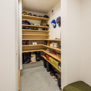 Ejemplo de armario vestidor unisex, minimalista, con armarios abiertos, suelo de cemento, suelo gris y puertas de armario de madera oscura
