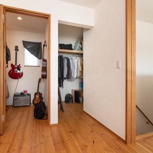 Diseño de armario vestidor bohemio con suelo de madera en tonos medios y suelo multicolor