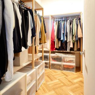 Esempio di una piccola cabina armadio unisex etnica con ante in legno chiaro, pavimento in compensato, pavimento marrone e soffitto in perlinato