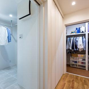 Idée de décoration pour un dressing neutre avec un sol en contreplaqué, un sol marron et un plafond en papier peint.