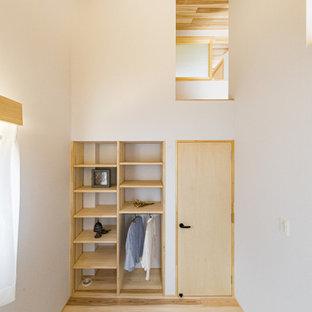 Imagen de armario unisex y madera, moderno, de tamaño medio, con armarios abiertos, puertas de armario beige, suelo de madera en tonos medios y suelo beige