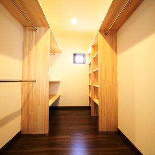 Immagine di una cabina armadio unisex moderna con nessun'anta, ante in legno scuro e parquet scuro
