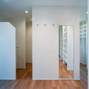 Ispirazione per una cabina armadio etnica con nessun'anta, ante bianche, pavimento in compensato e pavimento beige