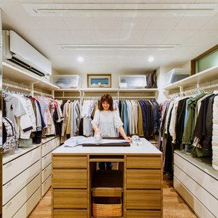 Imagen de armario vestidor unisex y papel pintado, actual, de tamaño medio, con suelo de madera en tonos medios, suelo marrón, papel pintado, armarios abiertos y puertas de armario blancas