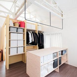 Exempel på en industriell garderob, med öppna hyllor, skåp i mörkt trä, målat trägolv och brunt golv