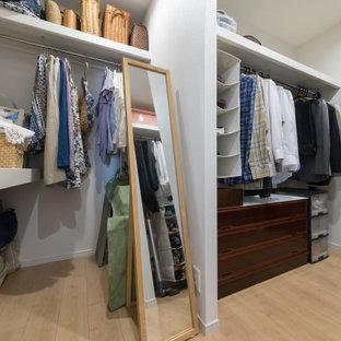 Ejemplo de armario vestidor unisex y papel pintado, minimalista, de tamaño medio, con armarios abiertos, suelo de contrachapado, suelo beige y papel pintado