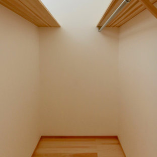 Idee per una cabina armadio unisex etnica di medie dimensioni con nessun'anta, pavimento in legno massello medio e pavimento bianco