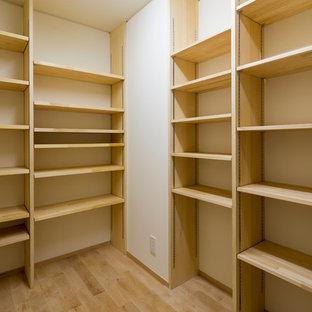 Immagine di una cabina armadio etnica con nessun'anta e ante in legno chiaro
