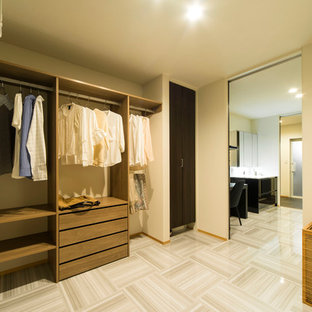 Foto de armario y vestidor minimalista, grande, con armarios abiertos, puertas de armario de madera oscura y suelo beige