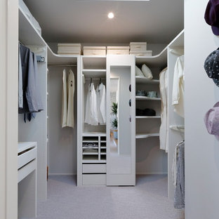 Design ideas for a large modern gender-neutral walk-in wardrobe in Other with carpet, grey floor, open cabinets and white cabinets.
