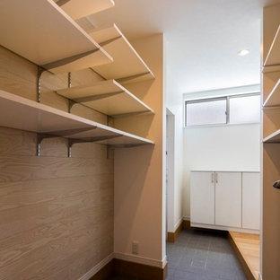 Diseño de armario vestidor unisex, escandinavo, de tamaño medio, con armarios abiertos, puertas de armario blancas, suelo de baldosas de porcelana y suelo azul