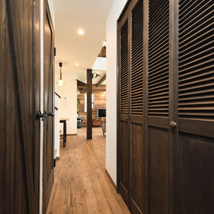 Photo of a large asian gender-neutral built-in wardrobe in Tokyo Suburbs with louvered cabinets, brown cabinets, medium hardwood floors and brown floor.
