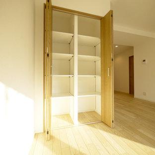Cette image montre un placard dressing nordique avec des portes de placard en bois brun, un sol en contreplaqué, un sol beige et un plafond en papier peint.
