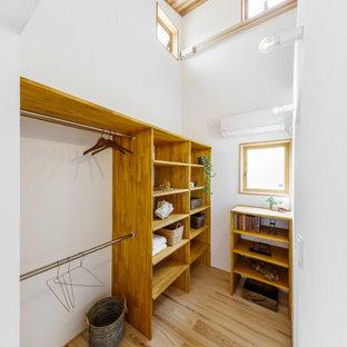 Modelo de armario y vestidor unisex y madera, minimalista, de tamaño medio, con armarios abiertos, puertas de armario marrones, suelo de madera en tonos medios y suelo beige