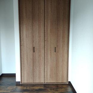 Foto de armario unisex y papel pintado, minimalista, pequeño, con armarios con paneles lisos, puertas de armario de madera en tonos medios, suelo vinílico, suelo marrón y papel pintado