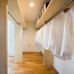 Diseño de armario vestidor unisex y papel pintado, minimalista, de tamaño medio, con armarios abiertos, suelo de madera clara, suelo beige y papel pintado