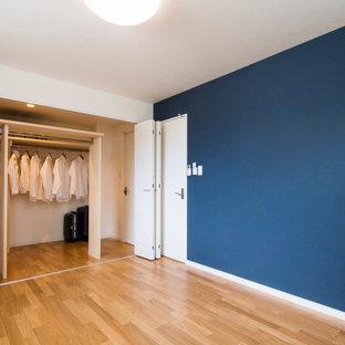 Imagen de armario vestidor unisex y papel pintado, minimalista, de tamaño medio, con armarios abiertos, suelo de madera clara, suelo beige y papel pintado