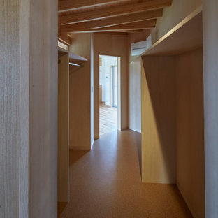 Esempio di una cabina armadio unisex etnica con nessun'anta, ante in legno chiaro, pavimento in linoleum, pavimento marrone e travi a vista