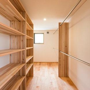 Idee per una cabina armadio etnica con nessun'anta, ante in legno scuro, pavimento in legno massello medio e pavimento marrone