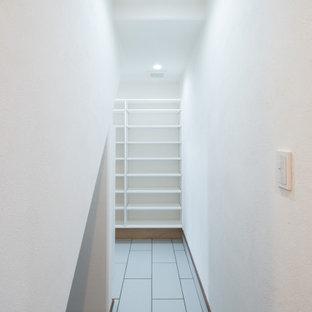 Modelo de armario vestidor unisex, campestre, grande, con armarios abiertos, puertas de armario blancas, suelo de baldosas de porcelana y suelo rojo