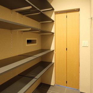 Diseño de armario vestidor unisex, pequeño, con armarios abiertos, puertas de armario grises, suelo de baldosas de porcelana y suelo gris