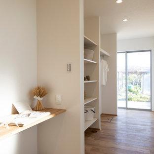 Imagen de armario unisex y papel pintado con armarios abiertos, puertas de armario blancas, suelo de madera en tonos medios y papel pintado