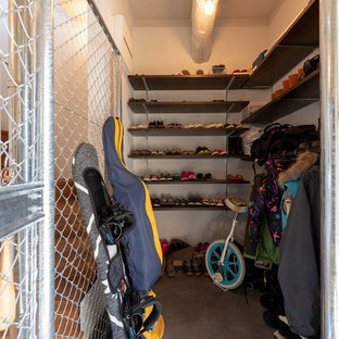Diseño de armario vestidor unisex, industrial, con armarios abiertos, puertas de armario de madera en tonos medios, suelo de cemento y suelo gris