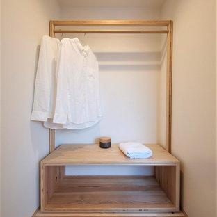 Exempel på ett litet asiatiskt walk-in-closet för könsneutrala, med mellanmörkt trägolv, brunt golv, öppna hyllor och beige skåp