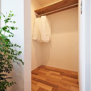 Imagen de armario vestidor unisex, asiático, pequeño, con armarios abiertos, puertas de armario beige, suelo de madera en tonos medios y suelo marrón