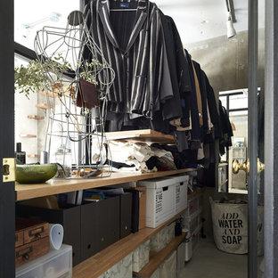 Diseño de armario vestidor industrial con armarios abiertos, puertas de armario de madera oscura, suelo de cemento y suelo gris