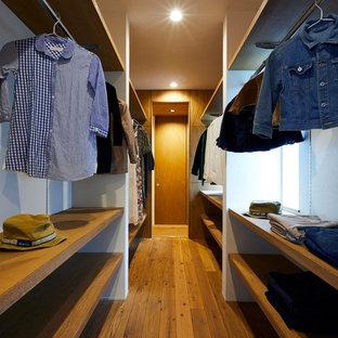 Cette image montre un dressing room minimaliste de taille moyenne et neutre avec un placard sans porte, des portes de placard marrons, un sol en bois foncé et un sol marron.