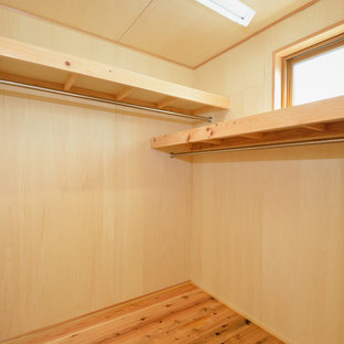 This is an example of a small world-inspired walk-in wardrobe in Other with light hardwood flooring.