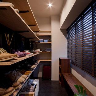 Esempio di una piccola cabina armadio contemporanea con nessun'anta, ante in legno scuro e pavimento nero